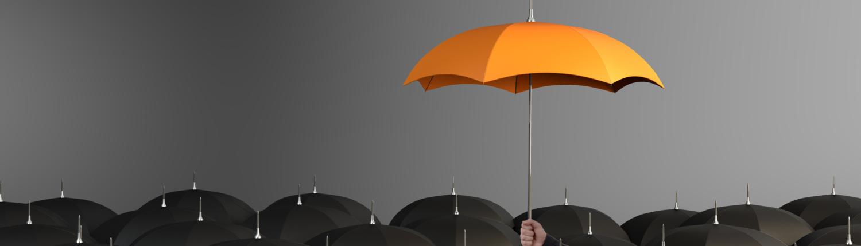 orange umbrella above regular black ones
