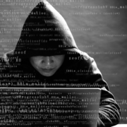 man with a hood sitting at a laptop with code text in white overlaid